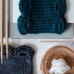 Two Marilue Cowls are stacked on books with knitting needles. Colors shown are teal and grey.