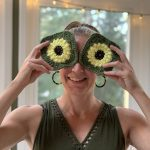 A goofy woman stand facing the camera except she's holding up 2 sunflower granny squares over her face like eyes.